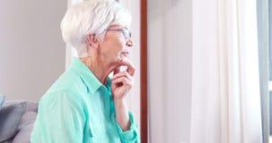 Donna senior premurosa che guarda attraverso la finestra archivi video