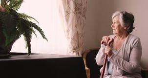 Donna senior premurosa che guarda attraverso la finestra video d archivio