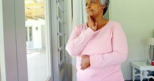 Donna senior premurosa che guarda attraverso la sala 4k della finestra a letto video d archivio