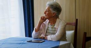 Donna senior premurosa che si siede alla tavola 4k stock footage