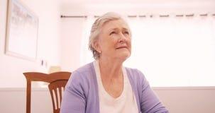 Donna senior premurosa che si siede a casa archivi video