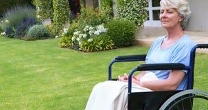 Donna senior premurosa che si siede in sedia a rotelle stock footage