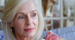 Donna senior premurosa che si siede sul sofà a casa 4k video d archivio