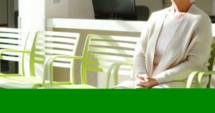 Donna senior premurosa che si siede sulla sedia in ingresso video d archivio