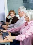Donna senior sicura che si siede con i compagni di classe allo scrittorio del computer Immagini Stock