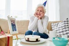 Donna senior sola che celebra compleanno fotografia stock