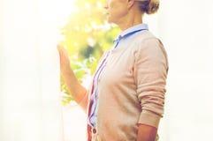 Donna senior sola che guarda attraverso la finestra a casa fotografie stock libere da diritti
