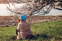 Donna senior sola che si rilassa nel giardino di primavera Concetto di giorno del ` s della madre fotografia stock