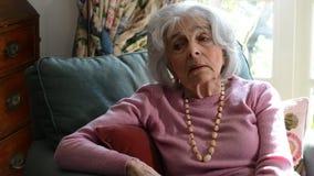 Donna senior sola che si siede in poltrona a casa video d archivio