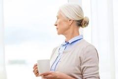 Donna senior sola con la tazza di tè o di caffè immagini stock libere da diritti
