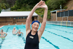 Donna senior sorridente che excerising al poolside Immagine Stock
