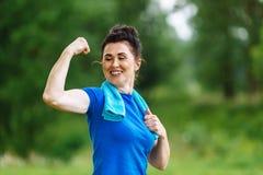 Donna senior sorridente che flette i muscoli all'aperto in parco Femmina anziana che mostra il bicipite Concetto coperto di erica Immagini Stock Libere da Diritti