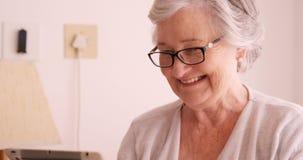 Donna senior sorridente che per mezzo della compressa digitale video d archivio