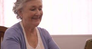 Donna senior sorridente che per mezzo della compressa digitale stock footage