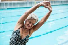 Donna senior sorridente che si esercita al poolside Immagini Stock