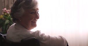 Donna senior sorridente che si siede sulla sedia a rotelle archivi video
