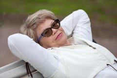 Donna senior sorridente che si trova sul banco nel vestito bianco di sport, esercizi all'allenamento Fotografia Stock Libera da Diritti