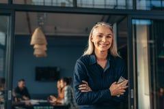Donna senior sorridente che sta in entrata dell'ufficio immagini stock libere da diritti