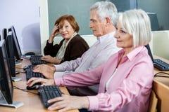 Donna senior sorridente con i compagni di classe allo scrittorio del computer Immagini Stock Libere da Diritti