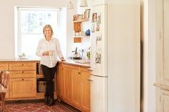 Donna senior sorridente nella sua cucina luminosa ed ordinata immagine stock