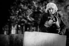 Donna senior triste con i fiori che fanno una pausa tomba immagine stock
