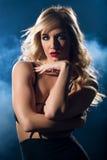 Donna sensuale che esamina macchina fotografica in un vestito da notte Immagine Stock