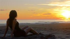 Donna sensuale che si rilassa guardando un bello tramonto su una spiaggia sabbiosa archivi video