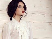 Donna sensuale con capelli scuri in vestiti eleganti che posano allo studio Fotografia Stock