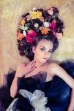 Donna sensuale con i fiori in suoi capelli che toccano il suo collo su oro Immagine Stock