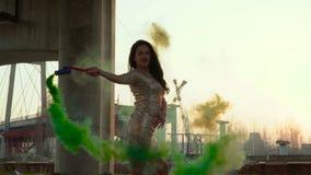 Donna sensuale nel dancing dorato del vestito sotto il ponte abbandonato con fumo verde video d archivio