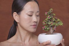 Donna senza camicia che tiene e che esamina una piccola pianta in un vaso di fiore, colpo dello studio Fotografia Stock Libera da Diritti