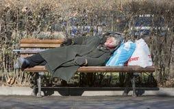 Donna senza tetto che dorme su un banco Fotografie Stock