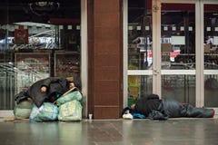 Donna senza tetto che dorme sulle borse e sulle buste Fotografia Stock
