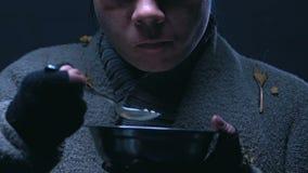 Donna senza tetto che mangia e che trema con il freddo, carità dell'alimento per la gente povera stock footage