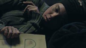 Donna senza tetto che tiene il segno di aiuto, programmi sociali di carità per la gente di reddito basso archivi video