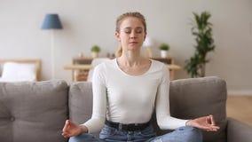 Donna serena calma che si siede sullo strato che medita a casa archivi video