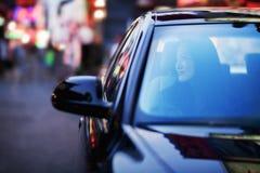Donna serena che osserva attraverso la finestra di automobile la vita notturna della città Fotografia Stock Libera da Diritti