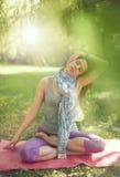 Donna serena e pacifica che pratica consapevolezza conscia meditando in natura con il chiarore del sole Fotografia Stock Libera da Diritti