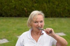 Donna serena senior che morde sul ferro Fotografia Stock Libera da Diritti