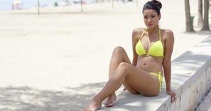 Donna seria in bikini giallo che si siede vicino alla spiaggia archivi video