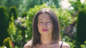 Donna seria calma che esamina macchina fotografica di estate di aria aperta del parco, vento del movimento lento archivi video