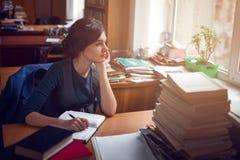 Donna seria che pensa nel silenzio delle biblioteche Fotografia Stock Libera da Diritti