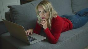 Donna seria con il computer portatile che si trova sullo strato video d archivio