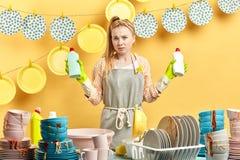 Donna seria infelice con i detersivi per i piatti che posano alla macchina fotografica fotografie stock