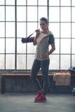 Donna seria in stuoia di yoga della tenuta dell'ingranaggio di allenamento nella palestra del sottotetto Fotografie Stock Libere da Diritti