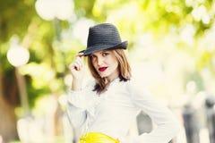 Donna sessuale in cappello, chiamante gesto, all'aperto Fotografia Stock