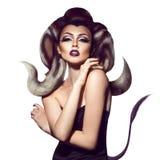 Donna sessuale del diavolo con i corni che esaminano macchina fotografica Immagini Stock Libere da Diritti