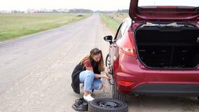 Donna sessualmente vestita che rotola ruota di riserva sulla strada stock footage