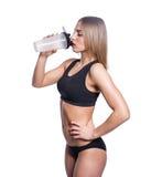 Donna sexy attraente dopo l'allenamento con l'agitatore isolato sopra fondo bianco La ragazza in buona salute beve il proteina de Immagini Stock