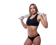 Donna sexy attraente dopo l'allenamento con l'asciugamano isolato sopra fondo bianco Giovane femmina con l'ente muscolare Fotografia Stock